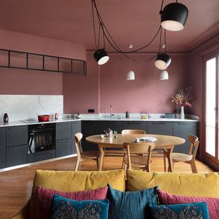 Cette photo montre une très grande cuisine ouverte linéaire tendance avec des portes de placard noires, un plan de travail en marbre, une crédence en marbre, un placard à porte plane, une crédence grise, un sol en bois brun, aucun îlot, un sol marron et un plan de travail gris.