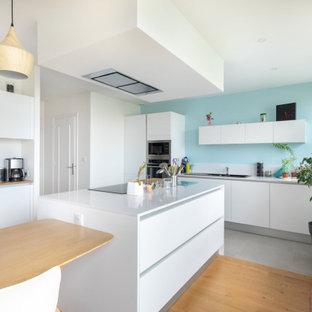 Cette image montre une cuisine américaine design avec un évier posé, un placard à porte plane, des portes de placard blanches, un électroménager en acier inoxydable, un îlot central, un sol gris et un plan de travail blanc.