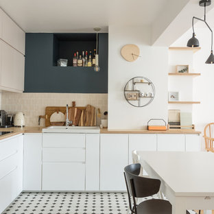 This is an example of a large scandinavian l-shaped open plan kitchen in Paris with white cabinets, wood benchtops, beige splashback, ceramic floors, no island, an integrated sink, porcelain splashback, beige benchtop, flat-panel cabinets, stainless steel appliances and multi-coloured floor.