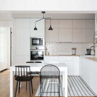 Photo of a mid-sized scandinavian l-shaped eat-in kitchen in Paris with a drop-in sink, flat-panel cabinets, grey cabinets, wood benchtops, beige splashback, ceramic splashback, stainless steel appliances, no island, beige benchtop, ceramic floors and multi-coloured floor.