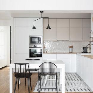 パリの中サイズの北欧スタイルのおしゃれなキッチン (ドロップインシンク、フラットパネル扉のキャビネット、グレーのキャビネット、木材カウンター、ベージュキッチンパネル、セラミックタイルのキッチンパネル、シルバーの調理設備の、アイランドなし、ベージュのキッチンカウンター、セラミックタイルの床、マルチカラーの床) の写真