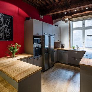Cette photo montre une cuisine américaine tendance en U de taille moyenne avec des portes de placard grises et une péninsule.