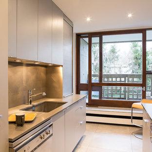 Exemple d'une cuisine parallèle tendance avec un évier encastré, un plan de travail en quartz, une crédence grise, un électroménager en acier inoxydable, un plan de travail gris, un placard à porte plane, des portes de placard beiges et un sol beige.