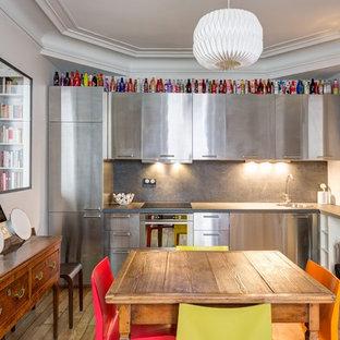 Aménagement d'une cuisine américaine éclectique en L de taille moyenne avec un évier 1 bac, une façade en inox, une crédence grise, un électroménager en acier inoxydable, un sol en bois clair et aucun îlot.