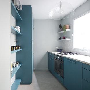 Cette image montre une cuisine parallèle design avec un placard à porte plane, des portes de placard bleues, un électroménager noir, aucun îlot, un sol beige, un plan de travail blanc, une crédence bleue et béton au sol.