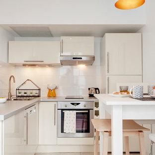 Idée de décoration pour une petit cuisine américaine design en L avec un placard à porte plane, des portes de placard blanches, une crédence blanche, une crédence en carreau de céramique et un électroménager encastrable.