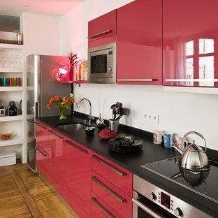 Cette photo montre une cuisine ouverte linéaire tendance de taille moyenne avec des portes de placard rouges, un sol en bois brun et aucun îlot.