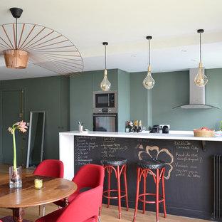 Idées déco pour une cuisine américaine parallèle contemporaine avec un placard à porte plane, des portes de placards vertess, un plan de travail en quartz, un électroménager en acier inoxydable, un sol en bois clair, un sol beige, un plan de travail blanc et une péninsule.