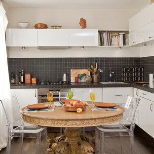 Exemple d'une cuisine américaine tendance en L de taille moyenne avec un placard à porte plane, des portes de placard blanches, une crédence noire et un sol en bois foncé.