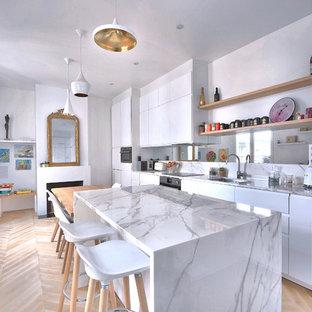 На фото: параллельная кухня в современном стиле с обеденным столом, врезной раковиной, плоскими фасадами, белыми фасадами, белым фартуком, фартуком из зеркальной плитки, техникой из нержавеющей стали, светлым паркетным полом, островом, бежевым полом, белой столешницей и мраморной столешницей с