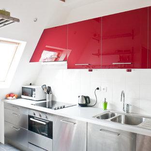 Geschlossene, Einzeilige, Mittelgroße Moderne Küche ohne Insel mit Doppelwaschbecken, flächenbündigen Schrankfronten, roten Schränken, Küchenrückwand in Weiß und Küchengeräten aus Edelstahl in Paris
