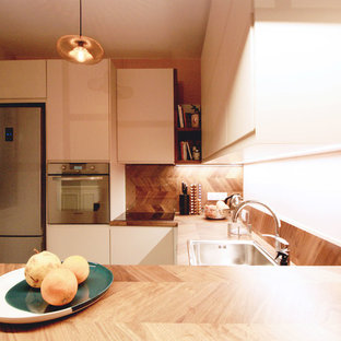 Mid-sized contemporary u-shaped eat-in kitchen in Paris with an undermount sink, beaded inset cabinets, beige cabinets, wood benchtops, brown splashback, timber splashback, stainless steel appliances, cement tiles, with island and turquoise floor.