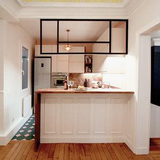 パリの中くらいのコンテンポラリースタイルのおしゃれなキッチン (一体型シンク、インセット扉のキャビネット、ベージュのキャビネット、木材カウンター、木材のキッチンパネル、パネルと同色の調理設備、セメントタイルの床、ターコイズの床) の写真