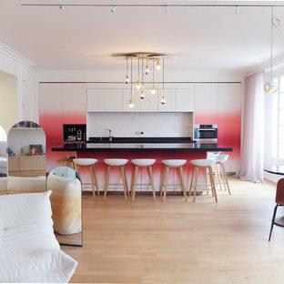 Offene, Einzeilige, Große Moderne Küche mit Unterbauwaschbecken, roten Schränken, Granit-Arbeitsplatte, Küchenrückwand in Weiß, Rückwand aus Marmor, Küchengeräten aus Edelstahl, hellem Holzboden, Kücheninsel, schwarzer Arbeitsplatte, flächenbündigen Schrankfronten und beigem Boden in Paris