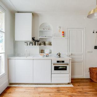 Exemple d'une petite cuisine linéaire tendance avec un évier posé, un placard à porte plane, des portes de placard blanches, une crédence blanche, un électroménager blanc, un sol en bois brun, un sol marron et un plan de travail blanc.