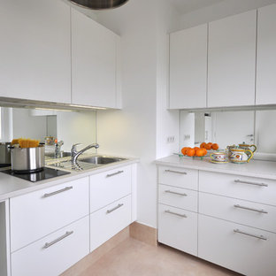 Small modern l-shaped kitchen in Paris with an integrated sink, flat-panel cabinets, white cabinets and mirror splashback.