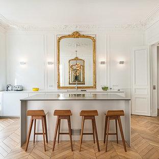 Inspiration pour une grande cuisine ouverte parallèle traditionnelle avec des portes de placard blanches, un sol en bois clair, un placard à porte plane, un îlot central, une crédence blanche et une crédence en bois.