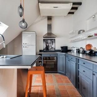 Idées déco pour une cuisine ouverte classique en U de taille moyenne avec un évier posé, un placard avec porte à panneau surélevé, des portes de placard bleues et un sol en carreau de terre cuite.