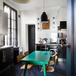 Пример оригинального дизайна интерьера: угловая кухня - столовая среднего размера в современном стиле с черными фасадами, белым фартуком и темным паркетным полом без острова