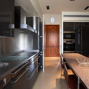 Idée de décoration pour une grande cuisine américaine linéaire design avec un placard à porte plane, des portes de placard noires, une crédence métallisée, un électroménager noir et un îlot central.