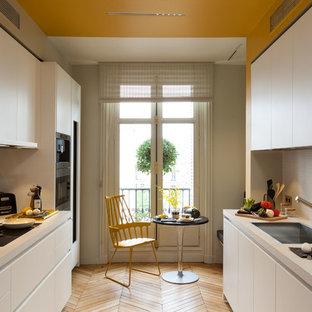Inspiration pour une cuisine parallèle design fermée et de taille moyenne avec un évier 1 bac, des portes de placard blanches, un électroménager encastrable, un sol en bois brun et aucun îlot.