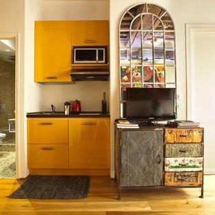 Exemple d'une petite cuisine ouverte linéaire éclectique avec un sol en bois clair, des portes de placard jaunes et aucun îlot.
