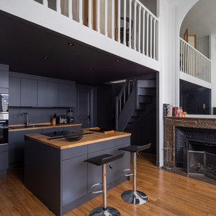 Aménagement d'une cuisine ouverte parallèle contemporaine avec un évier posé, un placard à porte plane, des portes de placard noires, un plan de travail en bois, un électroménager noir, un sol en bois brun, un îlot central, un sol marron et un plan de travail marron.