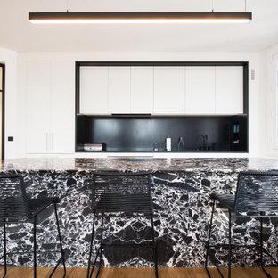 Idées déco pour une grand cuisine parallèle contemporaine avec un plan de travail en granite, une crédence noire, un sol en bois brun, un îlot central, un plan de travail noir, un placard à porte plane, des portes de placard blanches, une crédence en dalle de pierre, un électroménager encastrable et un sol marron.