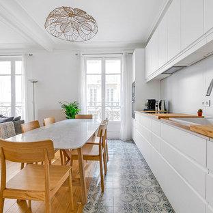Aménagement d'une grande cuisine ouverte linéaire scandinave avec un évier posé, des portes de placard blanches, un plan de travail en bois, une crédence blanche, une crédence en dalle métallique, un sol en carreaux de ciment, aucun îlot, un placard à porte plane, un sol gris et un plan de travail marron.