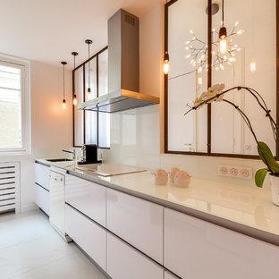 Cette photo montre une grande cuisine linéaire tendance fermée avec un évier 1 bac, des portes de placard blanches, une crédence blanche, un électroménager blanc, aucun îlot, un placard à porte plane et une crédence en feuille de verre.