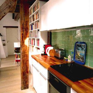 Idéer för att renovera ett mellanstort funkis kök, med en nedsänkt diskho, släta luckor, vita skåp, träbänkskiva, grönt stänkskydd, integrerade vitvaror och ljust trägolv