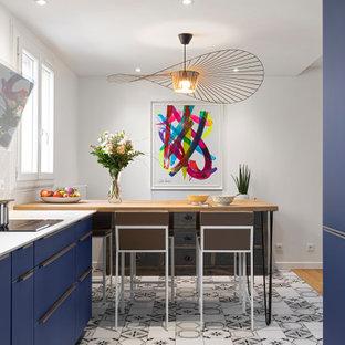 Inspiration pour une cuisine américaine design avec un placard à porte plane, des portes de placard bleues, un sol blanc et un plan de travail blanc.
