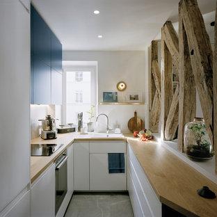 Inspiration för små moderna brunt kök, med en integrerad diskho, luckor med profilerade fronter, blå skåp, träbänkskiva, vitt stänkskydd, stänkskydd i marmor, rostfria vitvaror, klinkergolv i keramik och grått golv