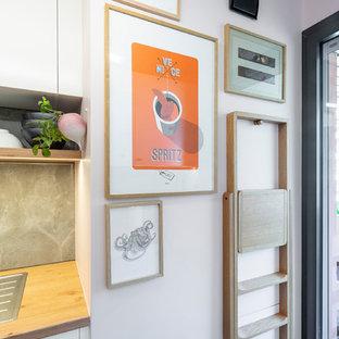パリの中くらいのモダンスタイルのおしゃれなII型キッチン (シングルシンク、インセット扉のキャビネット、白いキャビネット、ラミネートカウンター、グレーのキッチンパネル、セラミックタイルのキッチンパネル、セラミックタイルの床、アイランドなし、グレーの床、茶色いキッチンカウンター) の写真