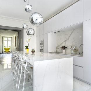 Aménagement d'une cuisine parallèle contemporaine fermée avec un placard à porte plane, des portes de placard blanches, une crédence blanche, une crédence en dalle de pierre, un îlot central et un sol blanc.