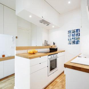 Idée de décoration pour une petite cuisine ouverte parallèle design avec un placard à porte plane, des portes de placard blanches, un plan de travail en bois, un électroménager blanc, un sol en bois clair, un évier encastré et aucun îlot.