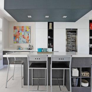 Idées déco pour une cuisine américaine contemporaine avec un placard à porte plane, des portes de placard grises, 2 îlots et un sol blanc.