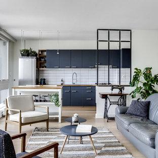 Cette image montre une cuisine ouverte linéaire nordique avec un placard à porte plane, des portes de placard bleues, un plan de travail en bois, une crédence blanche, une crédence en carrelage métro, un électroménager en acier inoxydable, un sol en bois clair, un îlot central et un sol beige.