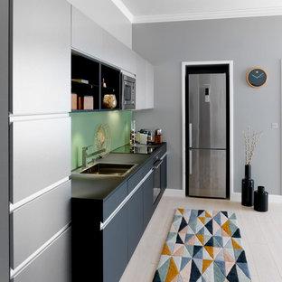Idée de décoration pour une cuisine ouverte linéaire design avec des portes de placard grises, un plan de travail en stratifié, une crédence verte, une crédence en feuille de verre, un électroménager en acier inoxydable et aucun îlot.