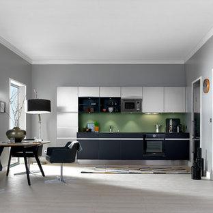 Réalisation d'une cuisine ouverte linéaire design de taille moyenne avec des portes de placard grises, un plan de travail en stratifié, une crédence verte, une crédence en feuille de verre, un électroménager en acier inoxydable, aucun îlot et un placard à porte affleurante.