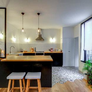 Exemple d'une cuisine tendance en U avec un évier de ferme, un placard à porte plane, des portes de placard noires, un plan de travail en bois, une crédence blanche, une crédence en carreau de céramique, un électroménager en acier inoxydable, une péninsule, un sol multicolore et un plan de travail beige.