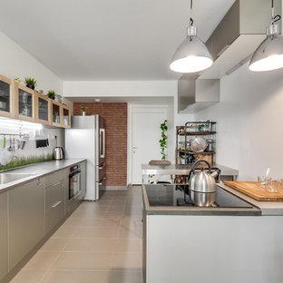 Aménagement d'une cuisine ouverte linéaire industrielle avec un évier encastré, un plan de travail en béton, une crédence verte, une crédence en feuille de verre, un électroménager en acier inoxydable, un sol en carrelage de céramique et un sol gris.