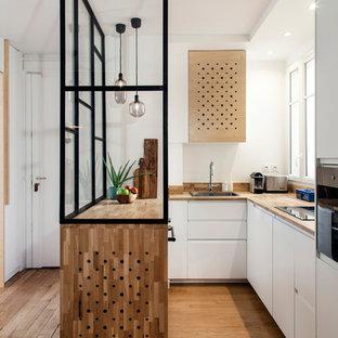 Cette image montre une cuisine design en U fermée avec un évier posé, un placard à porte plane, un plan de travail en bois, un électroménager en acier inoxydable, un sol en bois brun, un sol marron, une péninsule et des portes de placard blanches.