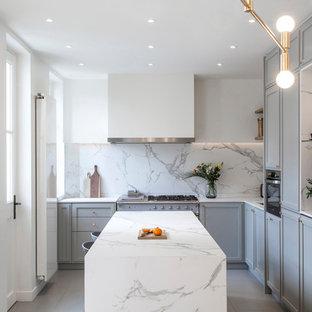 Idée de décoration pour une cuisine design en L avec un placard avec porte à panneau encastré, des portes de placard grises, une crédence blanche, une crédence en dalle de pierre, un îlot central, un sol gris et un plan de travail blanc.