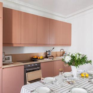 Cette image montre une cuisine américaine linéaire design avec un évier posé, un placard à porte plane, des portes de placard oranges, un plan de travail en bois, un électroménager en acier inoxydable, aucun îlot et un plan de travail beige.