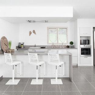 Exemple d'une cuisine américaine parallèle tendance de taille moyenne avec un évier posé, un placard à porte plane, des portes de placard blanches, un électroménager en acier inoxydable, un sol en carrelage de céramique, un îlot central et un sol gris.