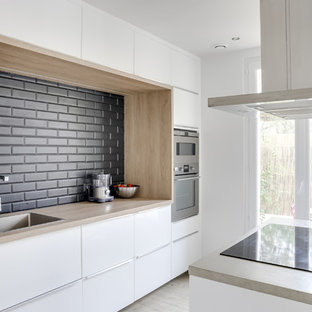 Design ideas for a contemporary galley eat-in kitchen in Marseille with concrete benchtops, black splashback, subway tile splashback, stainless steel appliances, ceramic floors, with island, an undermount sink, white cabinets and beige benchtop.