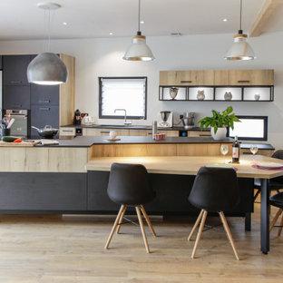 Cette image montre une cuisine parallèle design avec un évier encastré, un placard à porte plane, des portes de placard en bois clair, un électroménager en acier inoxydable, un sol en bois clair, un îlot central, un sol beige et un plan de travail gris.