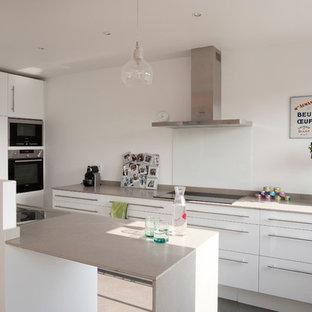 Cette image montre une cuisine ouverte design en U de taille moyenne avec un placard à porte plane, des portes de placard blanches, un électroménager en acier inoxydable et une péninsule.