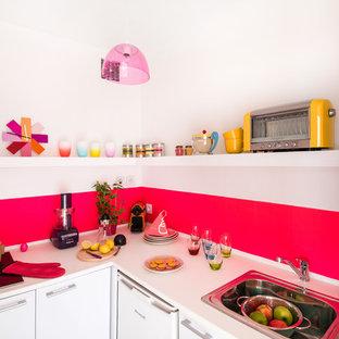 Réalisation d'une petite cuisine design en L fermée avec un évier posé, un placard à porte plane, des portes de placard blanches, une crédence rose, un électroménager blanc, un sol en bois foncé et aucun îlot.